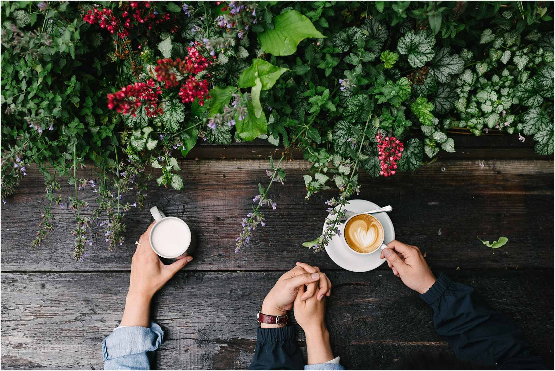 A couple holding hands with a latte.